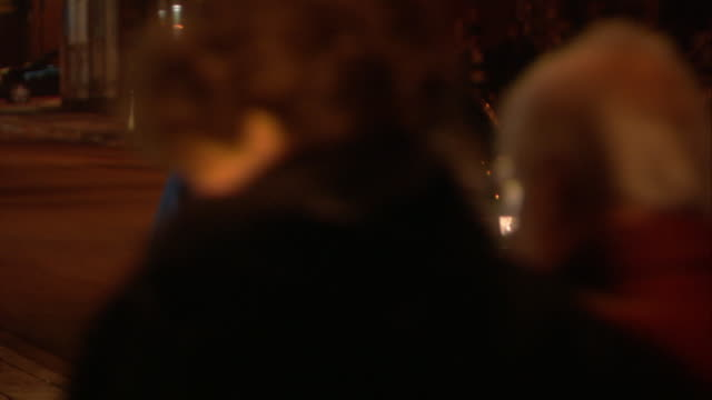 medium angle of pedestrians in winter attire walking down city street or main street. christmas lights visible. snow and ice on street. - targa con nome della via video stock e b–roll