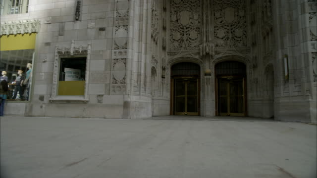 pan down of tribune tower, stone or concrete office building or skyscraper. neo-gothic architecture. - tribune tower stock-videos und b-roll-filmmaterial