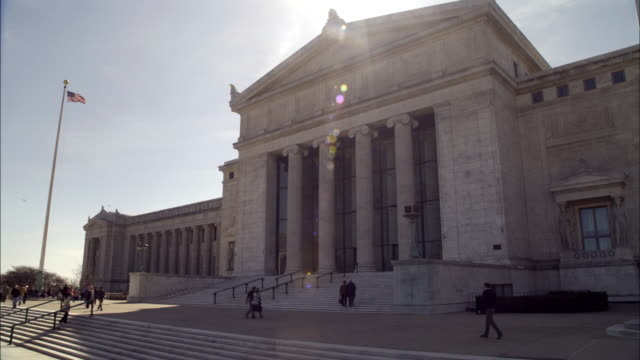wide angle of stone government office building. could be courthouse. marble columns or pillars. people standing on steps. american flag in bg. - 法廷点の映像素材/bロール