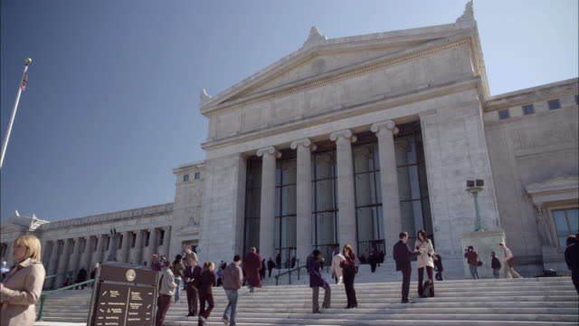 stockvideo's en b-roll-footage met pan down of news reporters and camera crews on steps outside of stone government office building. could be courthouse. marble columns or pillars. people standing on steps. american flag in bg. - gerechtsgebouw