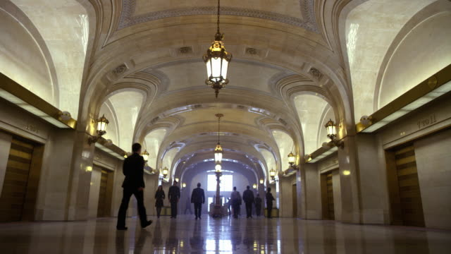 wide angle of people walking in hallway or lobby of marble stone building. could be government office building, hotel or courthouse. elevators. - government building stock videos and b-roll footage