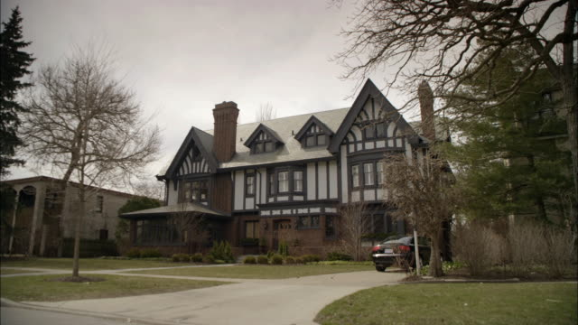wide angle of two story upper class house or mansion. grass, trees, shrubs, bushes in front yard. overcast sky. car in driveway. - stately home stock videos and b-roll footage