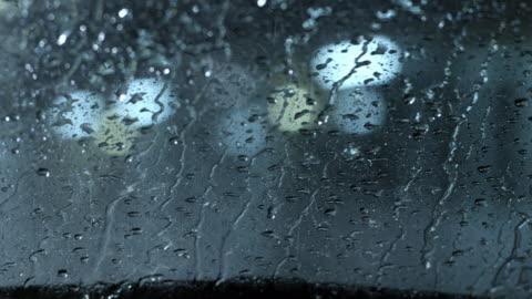vidéos et rushes de medium angle pov through windshield of car in parking lot or motel. rain, windshield wipers. - pare brise