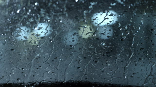 vídeos de stock e filmes b-roll de medium angle pov through windshield of car in parking lot or motel. rain, windshield wipers. - para brisas