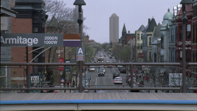 wide angle of el train passing through armitage station. elevated tracks. cars on city street in bg. multi-story brick office or apartment buildings. - elevated train stock videos and b-roll footage