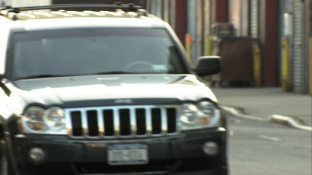 medium angle of jeep suv driving down city street. cars parked on curb. urban area. - 4x4 stock videos & royalty-free footage