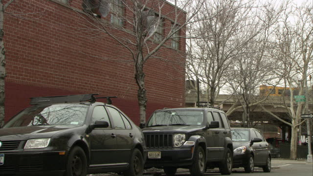 stockvideo's en b-roll-footage met medium angle of cars parked on curb of city street. overpass visible in bg. vw car drives by on street from bg to fg. bare branches on tree. brick building next to street. - bare tree
