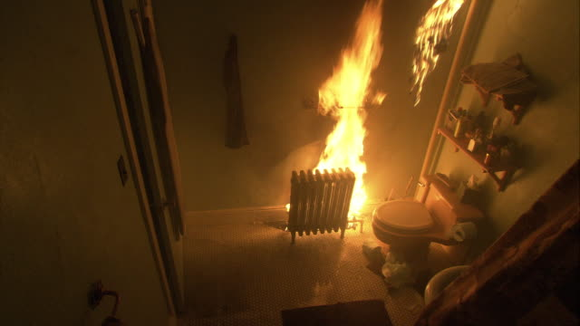 high angle down of radiator grille in bathroom raging with flames or fire. toilet and shelves visible in bathroom. towel hangs on wall. could be accident. - heizung stock-videos und b-roll-filmmaterial