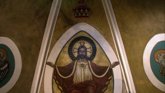 vidéos et rushes de pan up of mural or painting on domed ceiling of church. mural of jesus christ and crown. angel murals and statues visible. sculptures. religious art. - christianisme