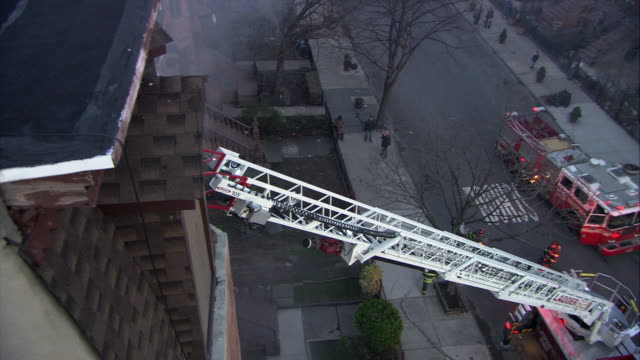 high angle down of hook and ladder fire trucks on city street leaned against building with smoke billowing out. could be fire. ladder leans up against building. firemen or firefighters visible on city street. could be apartment building. - fire engine stock videos & royalty-free footage