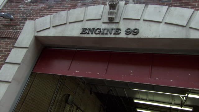 """up angle of sign over entrance to fire station garage reading """"engine 99."""" brick building. - fire station stock videos & royalty-free footage"""