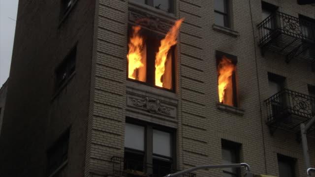vídeos y material grabado en eventos de stock de up angle of upper or middle class brick apartment building windows. fire rages from upper floor window. balconies visible on some apartments. - piso de edificio