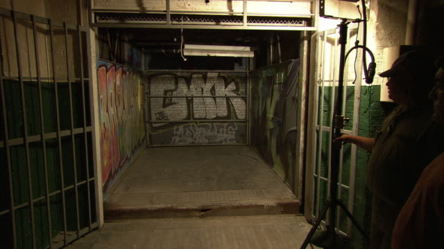medium angle of lights flickering as freight elevator goes down elevator shaft. graffiti. lower class building. - freight elevator stock videos & royalty-free footage