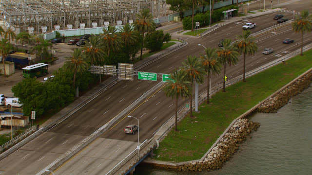 stockvideo's en b-roll-footage met aerial tracking of suv across macarthur causeway or freeway toward downtown miami. bridge over bay. dodge island, port or harbor. palm trees, tropical. skyscrapers and high rise office or apartment buildings. - macarthur causeway bridge