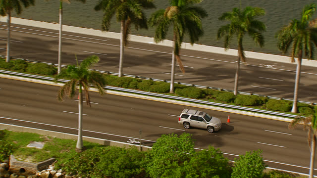 stockvideo's en b-roll-footage met aerial tracking shot of suv and cars driving across macarthur causeway or freeway. bridge over bay. tropical. - macarthur causeway bridge
