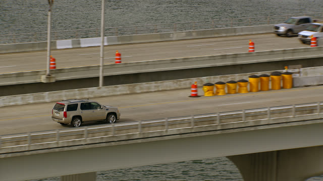 stockvideo's en b-roll-footage met aerial tracking shot of suv and cars driving across macarthur causeway or freeway. bridge over bay. tropical. skyscrapers and high rise office buildings of downtown miami city skyline. - macarthur causeway bridge