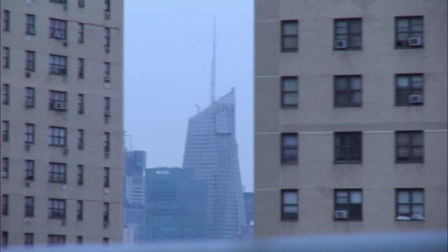 medium angle driving pov of cars, taxis driving on williamsburg bridge toward manhattan. pass brick buildings, apartment buildings with empire state building and citicorp building in bg. lower east side manhattan. - citigroup center manhattan stock videos & royalty-free footage