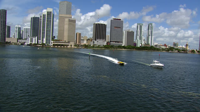 aerial of miami skyline. camera pushes in over ocean or bay to high rise hotels, condominiums, office buildings, and apartment building. speedboat visible moving towards camera leaving wake. boats moves past storage yard or shipyard with cranes and storag - motoscafo da competizione video stock e b–roll