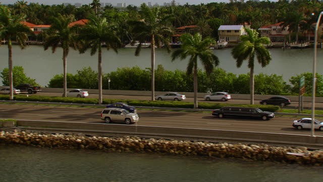 stockvideo's en b-roll-footage met aerial tracking shot of suv and cars driving over macarthur causeway, freeway or bridge over bay toward miami beach. high rise apartment buildings, condominiums or hotels. boats in marina. - macarthur causeway bridge