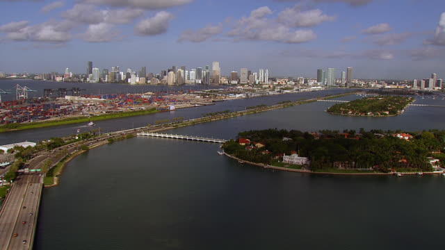 aerial of islands, star island, palm island and dodge island in bay. downtown miami city skyline in bg. port or industrial area. harbor or docks. tropical. - star island stock videos & royalty-free footage