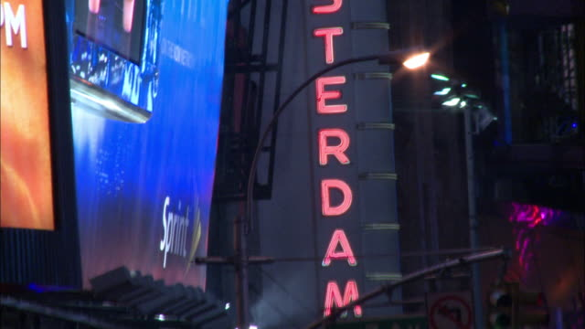 "pan down on ""amsterdam"" neon sign for new amsterdam theatre and sign for madame tussauds wax museum. flashing lights, neon lights, electronic billboards in times square. new york. - madame tussauds stock videos & royalty-free footage"