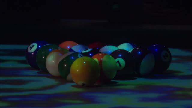 close angle of cue ball on pool table. could be in nightclub. psychedelic neon lights. people walk past table. games. could be bar. - pool table stock videos & royalty-free footage
