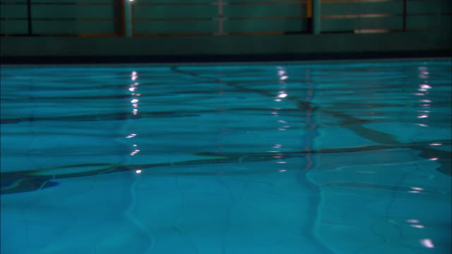 close angle of water in indoor swimming pool. underwater lanes visible. boy or man swims by. could be swimming practice. sports. - bath stock videos & royalty-free footage