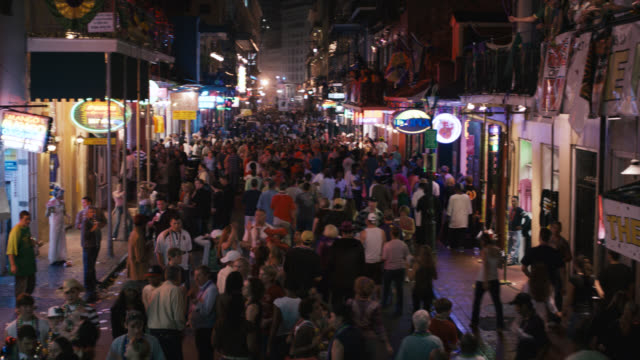 pan up of crowd of people on city street, could be bourbon street. mardi gras. party, celebration or festival. stores or shops, commercial area. - mardi gras stock videos and b-roll footage