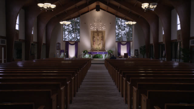 wide angle interior of church. pews, altar, and crucifix visible. statue or sculpture of jesus christ on cross visible in bg. could be man visible praying in pew. camera pans right to left to prayer candles on table. - 宗教上のシンボル点の映像素材/bロール