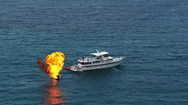aerial of two story upper class yacht on ocean. emergency life boat or speedboat attached to back of yacht. explosion and sparks on life boat. could be bomb. - motoscafo da competizione video stock e b–roll