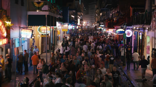 pan up of crowd of people on city street, could be bourbon street. mardi gras. party, celebration or festival. stores or shops, commercial area. - bourbon street new orleans stock videos and b-roll footage