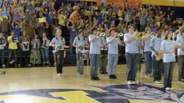 "medium angle of marching band standing in gymnasium during pep rally with students in bleachers or stands. sign on wall reads ""ojai north."" could be high school. students cheering and wave with signs, banners, and decorations. - marching band stock videos & royalty-free footage"