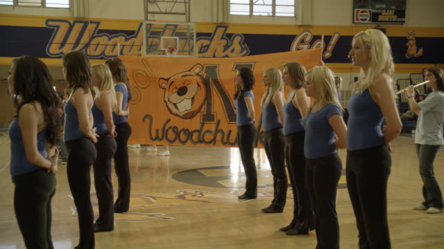 "pan up from wide angle of dance team or cheerleaders during pep rally to sign or banner reading ""go woodchucks go!"" could be high school. gymnasium. basketball hoops visible. girls dance and smile. flautist visible in bg. could be marching band. - cheerleader stock videos & royalty-free footage"