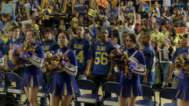medium angle of cheerleaders cheering at pep rally. men's basketball team visible. students visible on bleachers or in stands in bg cheering. students have signs, banners, and decorations. could be high school. - cheerleader stock videos & royalty-free footage
