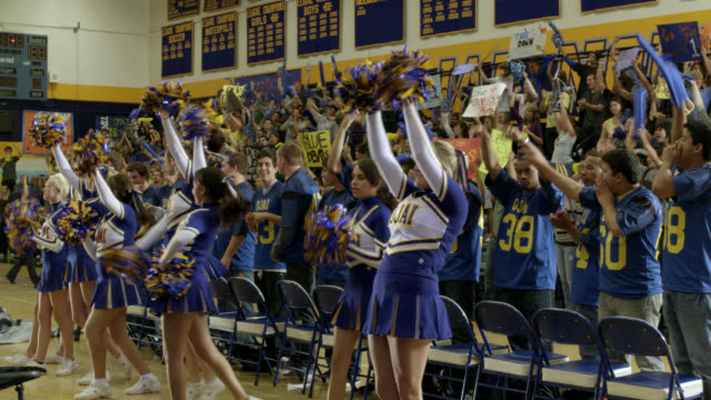 medium angle of cheerleaders cheering and dance team dancing at pep rally. men's basketball team visible. students visible on bleachers or in stands in bg cheering. students have signs, banners, and decorations. could be high school. - cheerleader stock videos & royalty-free footage