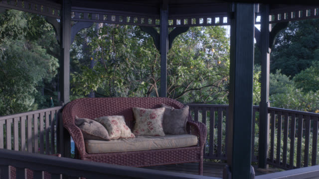 medium angle of interior of gazebo with patio couch. trees visible surrounding gazebo. could be back yard. swimming pool partially visible in bg. - gazebo stock videos & royalty-free footage