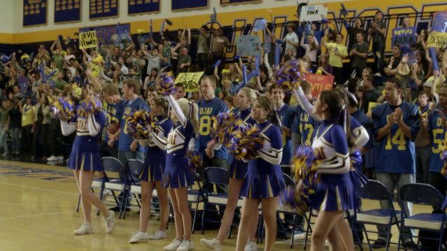 pan down from basketball hoop to cheerleaders cheering at pep rally. men's basketball team visible. students visible on bleachers or in stands in bg cheering. students have signs, banners, and decorations. could be high school. - cheerleader stock videos & royalty-free footage
