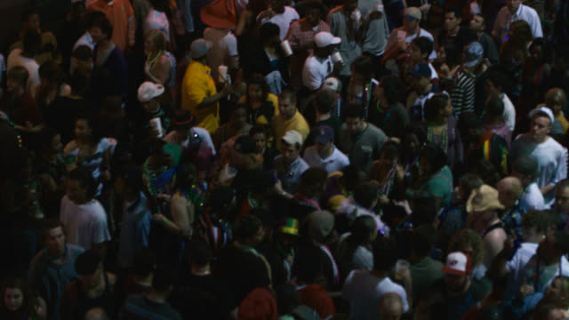 high angle down of crowd of people on city street, could be bourbon street. mardi gras. party, celebration or festival. stores or shops, commercial area. - mardi gras stock videos and b-roll footage