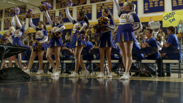 up angle of cheerleaders and basketball team at high school pep rally. students in stands or bleachers partially visible. signs or banner visible. mascot in beaver or woodchuck costume fall of ramp and lands on face on gym floor. stunts. - cheerleader stock videos and b-roll footage