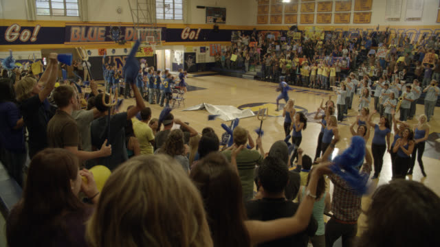 wide angle of students, crowds, cheering at pep rally. dancers, band, athletes. basketball court, gymnasium. mascot does jumping flip and dunks basketball into basket. - basketball player stock videos & royalty-free footage