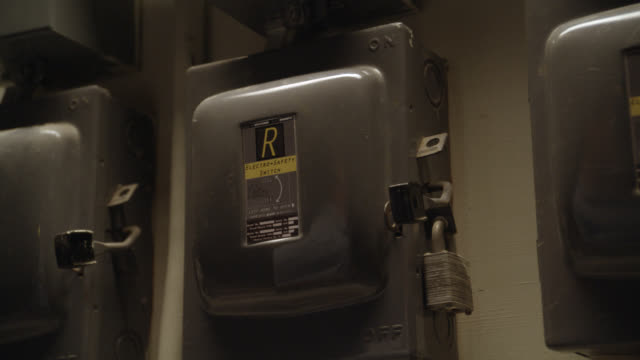 close angle of hand pulling down lever on circuit breaker or power boxes with locks or padlocks. could be basement. - lever stock videos & royalty-free footage