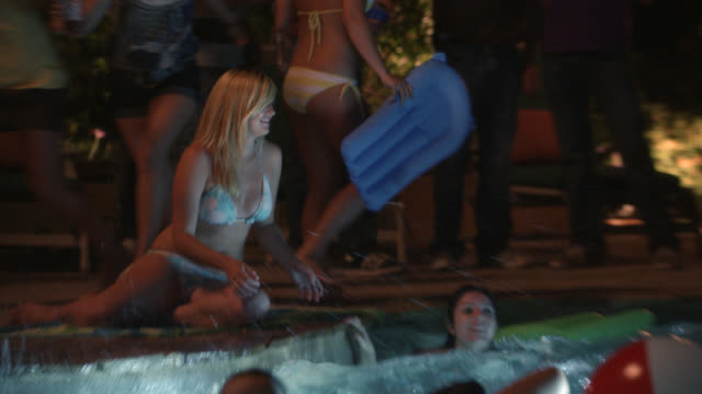 medium angle of teenagers at pool party. swimming pool. inflatable ball, towels, and bathing suits. teenager lies on raft in pool. teens jump in and splash in water. - jump ball stock videos and b-roll footage