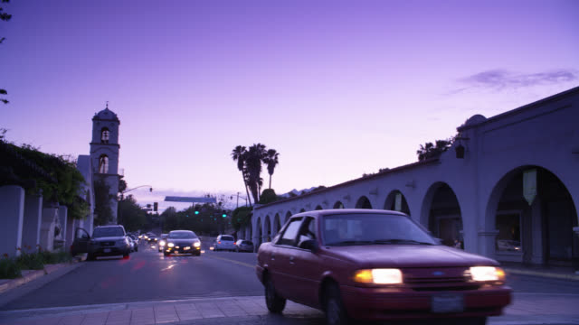 wide angle of cars driving on city street. pedestrians visible on sidewalk. bell tower in bg. spanish style architecture. downtown of small town.  palm trees visible. - ventura stock videos and b-roll footage