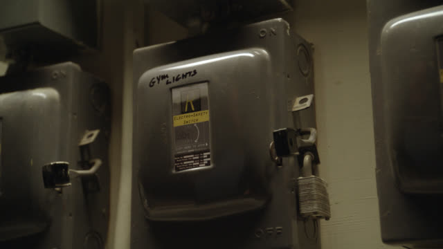 """close angle of hand pulling down lever on circuit breaker or power boxes with locks or padlocks. hand pushes lever back up. could be basement. writing on power box reads """"gym lights."""" could be school. - lever stock videos & royalty-free footage"""