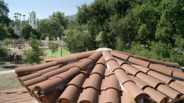 pan up from spanish style roof of gazebo or building to high angle down over park. trees and playground visible. spanish bell tower visible in bg. downtown ojai. camera pans back down roof of gazebo. - gazebo stock videos & royalty-free footage