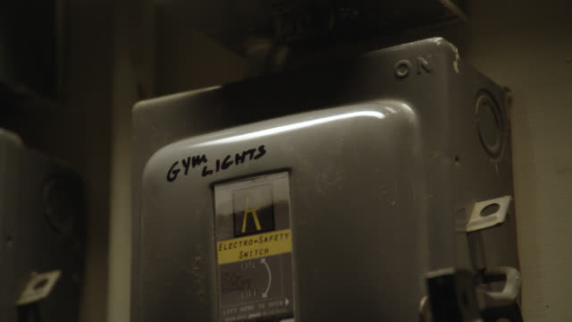 """close angle of hand pushing up lever on circuit breaker or power boxes with locks or padlocks. could be basement. hands pushes lever back up. series. writing on power box reads """"gym lights."""" could be school. - lever stock videos & royalty-free footage"""