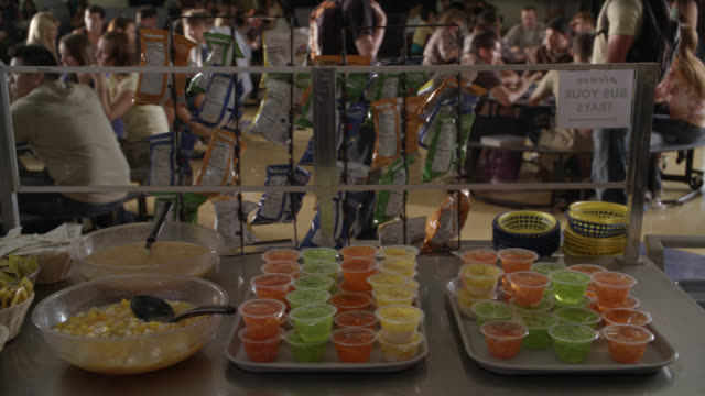 medium angle of fruit cups or fruit salad in cafeteria. students sitting at table in bg. - kantine stock-videos und b-roll-filmmaterial