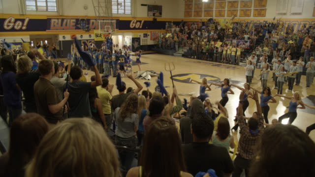 wide angle of students, crowds, cheering at pep rally. dancers, band, athletes. basketball court, gymnasium. mascot does jumping flip and dunks basketball in basket. stunt. - performer stock videos & royalty-free footage