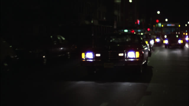 wide angle driving pov 3/4 right back of four-door car or sedan driving on city streets. commercial urban area. single police light flashing. unmarked police car. - police car stock videos and b-roll footage