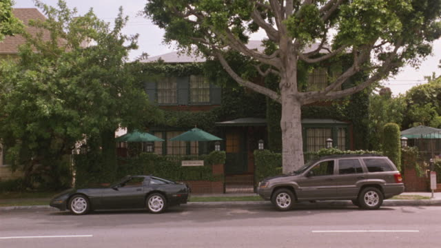 medium angle of two story upper class brick house with green accents. see brick wall covered with vines in front of house. see black corvette and grey suv parked in front of house. see green umbrellas in front of house. camera moves left. neg cut. could b - brick house stock videos & royalty-free footage